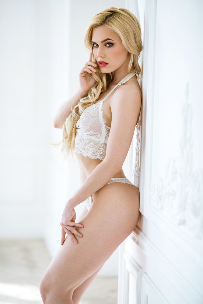 Fiona stood against a wall in white lingerie