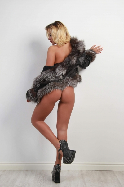 Blonde escort Cassie in a fur coat showing off her amazing bum