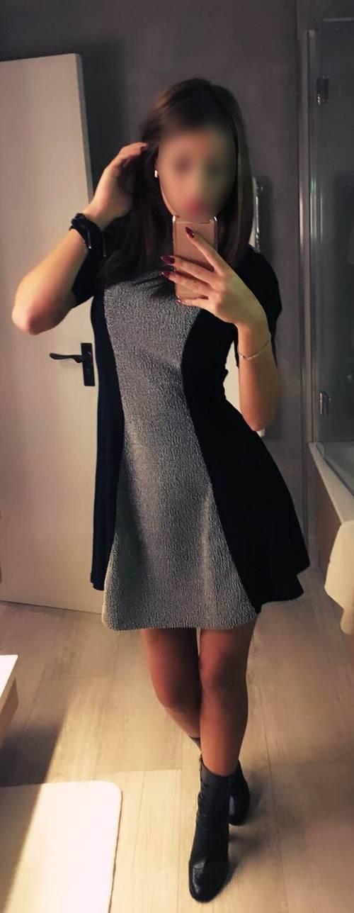 Mary taking a selfie in the mirror whilst wearing a grey and black dress