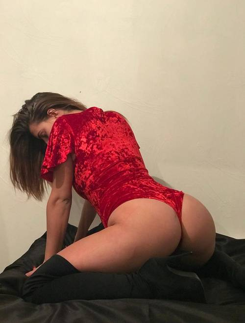 Jess bent over in a red velvet bodysuit