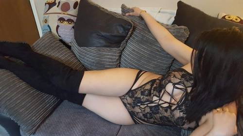 Aesha lay on a chair in a body stocking