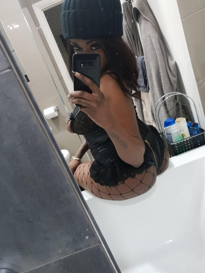 Nikki taking a picture in a mirror wearing very sexy leather underwear