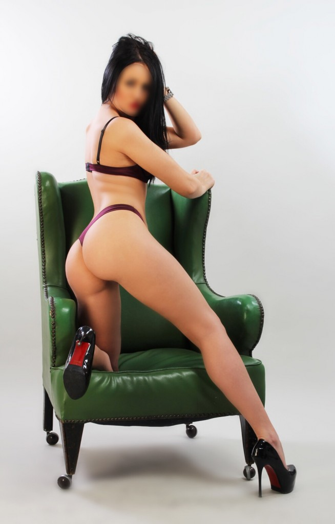 Mika wearing purple lingerie leaning on green chair showing her bum.
