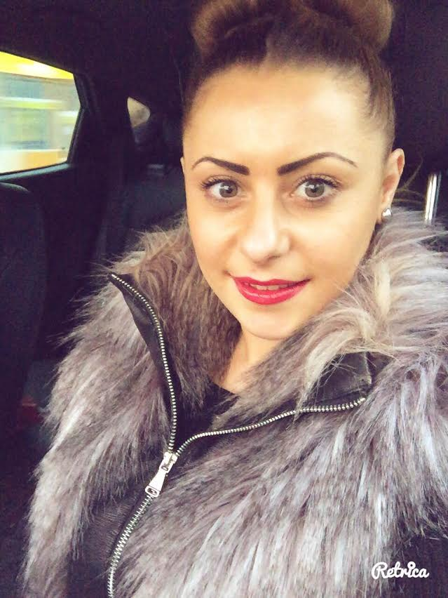 Selfie of Sasha wearing fluffy leather jacket and bright red lipstick with her hair in a bun.