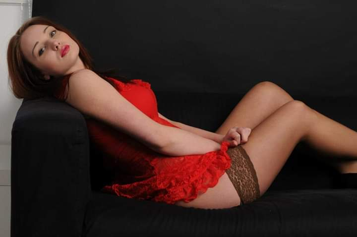 Alex lying on couch wearing sexy red lingerie and nude stockings.